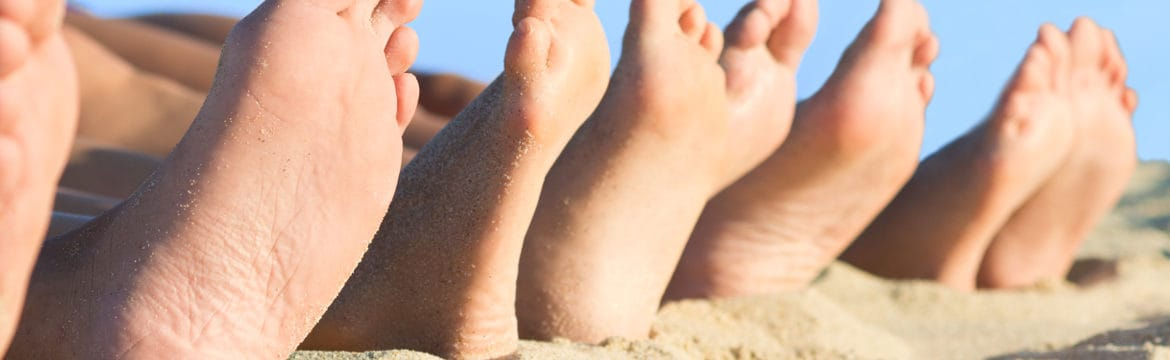 Kid's feet in a line on the beach